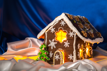 housetop: Christmas glazed gingerbread house with sweet pine and walnuts on housetop. Against blue silk background. Stock Photo