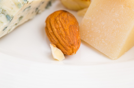 cheese platter: Assorted cheese platter with almonds. Close up.