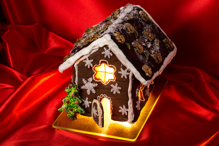 housetop: Christmas glazed gingerbread house with sweet pine and walnuts on housetop. Against red silk background.