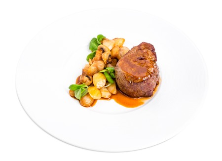 garnish: Delicious beef steak in demiglas sauce with vegetable garnish. Isolated on a white background.