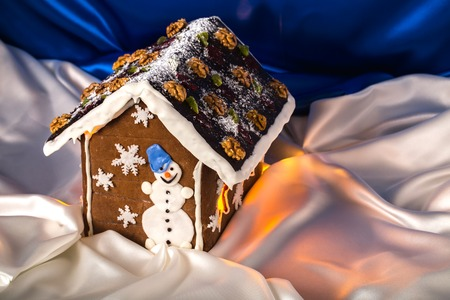 housetop: Christmas glazed gingerbread house with sugar snowman and walnuts on housetop. Against blue silk background.