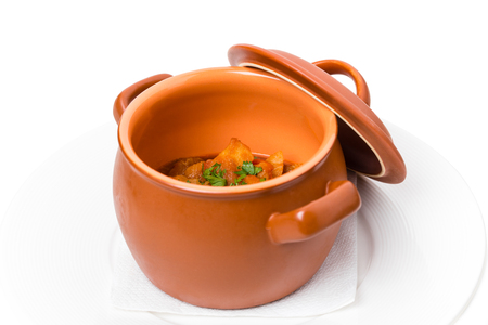 crock pot: Stewed pork and potatoes covered with minced herbs in crock pot. Isolated on a white background.