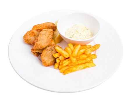 fish isolated: Traditional british fish and chips with tartar sauce and fresh lemon. Isolated on a white background.