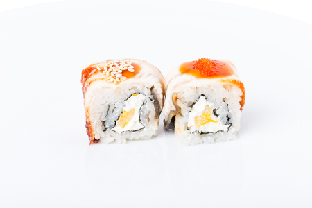 unagi: Traditional japanese sushi roll with smoked unagi and red tobiko caviar. Macro. Photo can be used as a whole background. Stock Photo