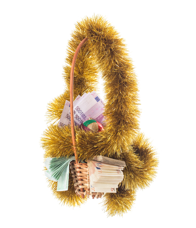 Wicker basket full of euro bills with christmas golden tinsel and bright Christmas ball. Isolated on a white background. Stock Photo