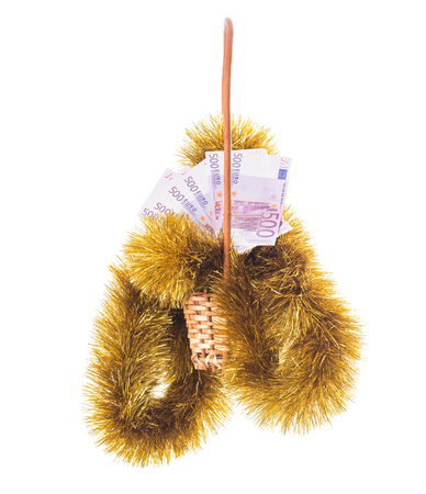 christmas debt: Wicker basket full of euro bills with christmas golden tinsel. Isolated on a white background. Stock Photo