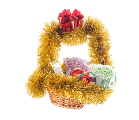 christmas debt: Wicker basket full of euro bills with christmas golden tinsel and red ribbon. Isolated on a white background. Stock Photo