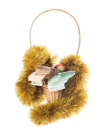 christmas debt: Wicker basket full of euro bills with christmas golden tinsel and bright Christmas ball. Isolated on a white background. Stock Photo