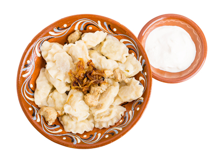 Russian dumplings pelmeni stuffed with meat and potatoes. Served with sour cream. Isolated on a white background.
