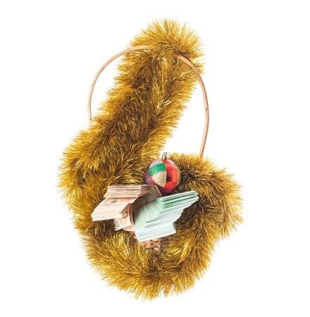 La cesta de mimbre llena de billetes en euros con el oropel de navidad de oro y brillante bola de Navidad. Aislado en un fondo blanco.