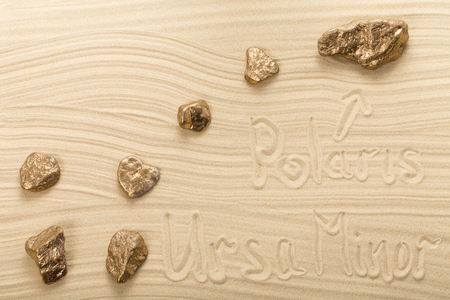 ursa minor: Golden stones in form of constellation Ursa Minor on waved sand. Photo can be used as a whole background.