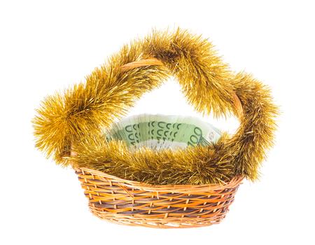 La cesta de mimbre llena de billetes en euros con el oropel de oro de la Navidad. Aislado en un fondo blanco.