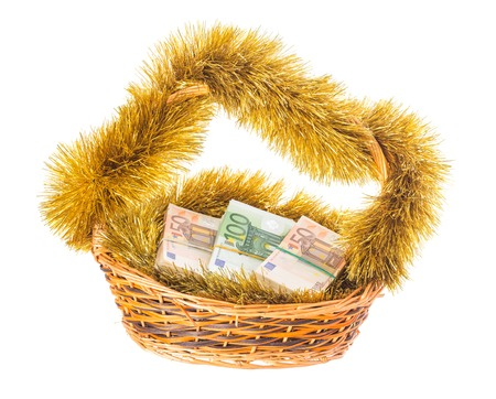 Wicker basket full of euro bills with christmas golden tinsel. Isolated on a white background. Stock Photo