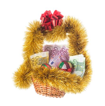 La cesta de mimbre llena de billetes en euros con el oropel de oro Navidad y la cinta roja. Aislado en un fondo blanco. Foto de archivo