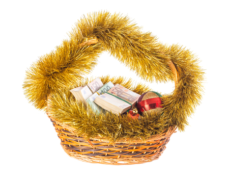 christmas debt: Wicker basket full of euro bills with christmas golden tinsel and bright Christmas balls. Isolated on a white background.