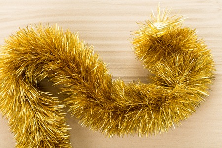 Golden christmas tinsel on waved sand. Macro. Photo can be used as a whole background. Stock Photo