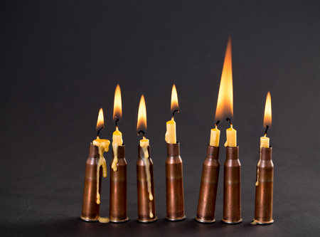 Burning candles and empty rifle cartridges. As a symbol of war and victims. Located on black cardboard as a background. Stock Photo