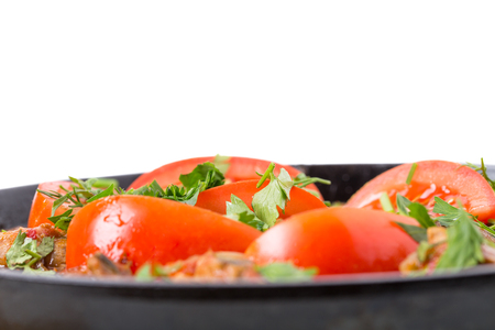 Delicious stewed pork fillet with fresh tomatoes and minced parsley in cast iron pan. Isolated on a white background.