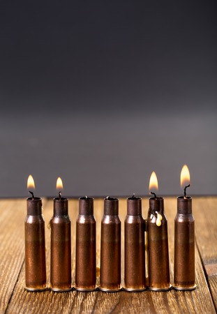 Burning candles and empty rifle cartridges. As a symbol of war and victims. Located on brown wooden table against black background. Stock Photo