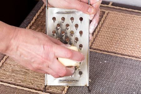 grating: Male hands grating butter for dough on a kitchen table as a background.
