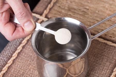 gelatine: Adding powdered gelatin to water in metal pot.
