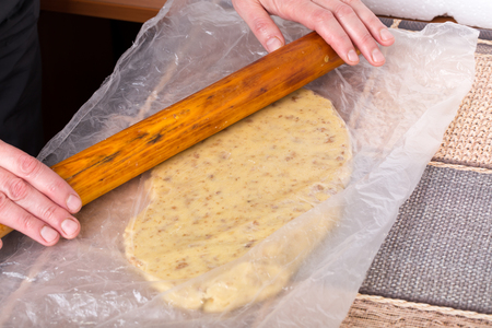 Hand with rolling pin roll out dough for cake.