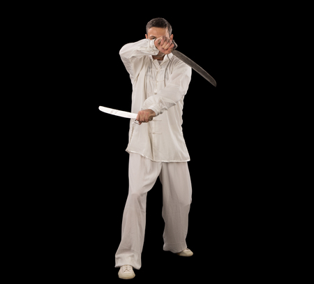 Man in white spining swords on a black backgrownd. 스톡 콘텐츠