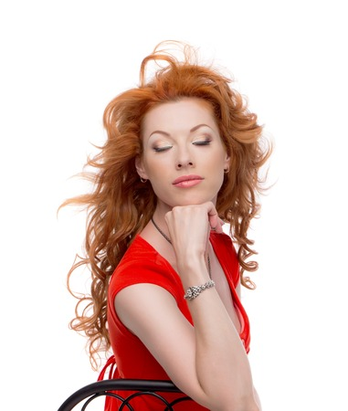 sholders: Redhead in a red dress in the chair with eyes closed.