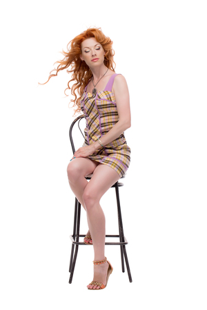 Fulllength shot of redhead sitting with eyes closed. Stock Photo