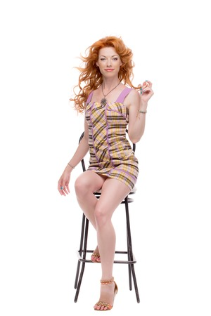 jewlery: Fulllength shot of redhead in a chair.