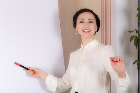 Business woman standing near the whiteboard with a marker. Photo can be used as a whole background.
