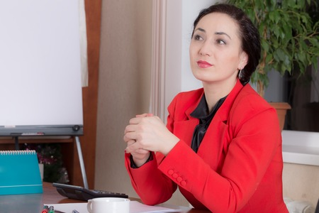 Business woman sitting at the office table. Photo can be used as a whole background.