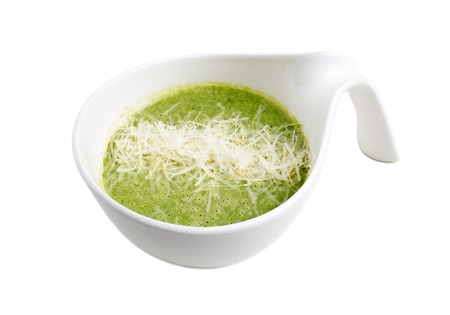 Delicious spinach cream soup with parmesan. Isolated on a white background.