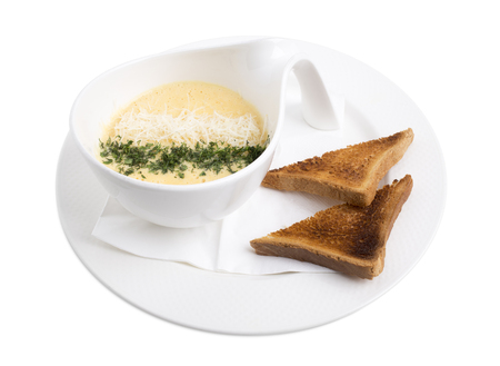 Cheese cream soup with herbs and roasted toasts. Isolated on a white background.
