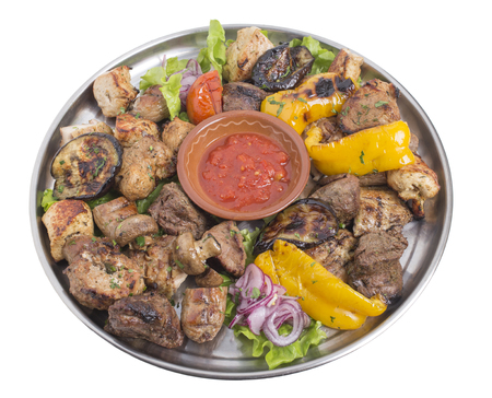 Assort of grilled meat and vegetables on a metal tray with tomato sauce. Isolated on a white background.