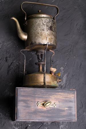 wood burner: Vintage metallic kettle on a wooden shelf.