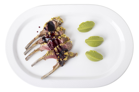 Roasted rack of lamb with pistachios and mint puree. Isolated on a white background.