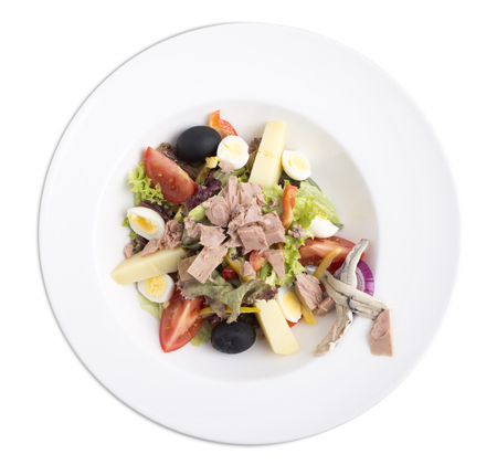Delicious nicoise tuna salad with eggs and vegetables. Isolated on a white background.