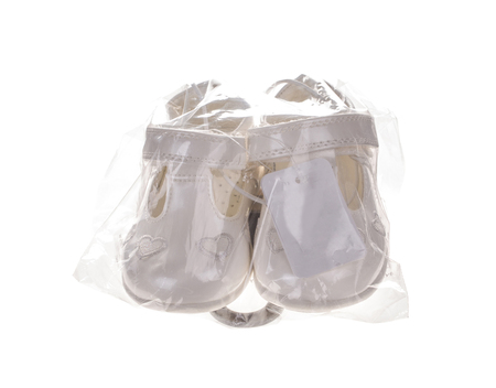 Childrens shoes in a plastic bag. Isolated on the white background. Stock Photo