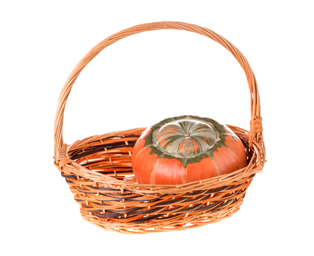 Composition of a pumpkin at the basket. Isolated on the white background. 版權商用圖片