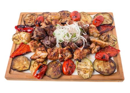 carnes y verduras: Mixed grilled meats platter with vegetables. Isolated on a white background. Foto de archivo