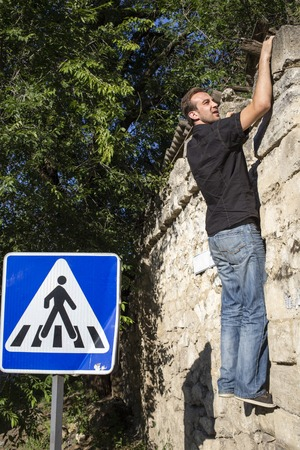 one lane sign: Man and a city. The young man is climbing on the wall.