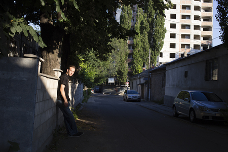 Person and city. A man is stood near a wall in the street.