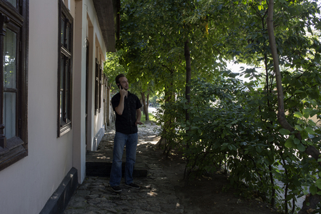 sidewalk talk: Person and city. A man is talking by a mobile phone in the street.