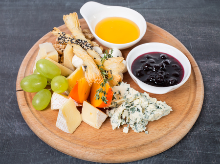 Cheese platter with honey and berry jam. Plate located on a black table as a background.