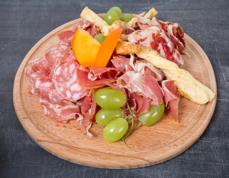 hams: Mixed italian dried meats platter with croutons and grapes. Plate located on a black table as a background.