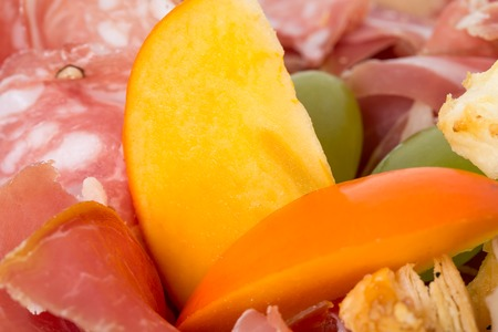 Mixed italian dried meats platter with mango. Macro. Photo can be used as a whole background. Stock Photo
