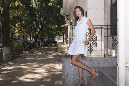 frock: Girl and city. There is a picture of an young woman is on the streets.