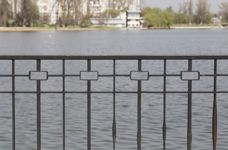 Hammered fencing and body of water. It is located on the blurred background.