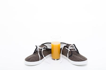 vaso de precipitado: Jugo y zapatillas Situado en el fondo blanco. Foto de archivo